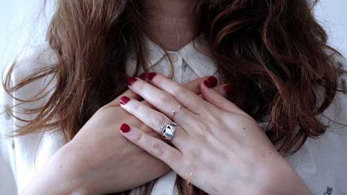 mujer con anillo de compromiso y manos en pecho